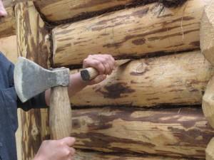 Фото: процесс конопатки деревянного дома джутом
